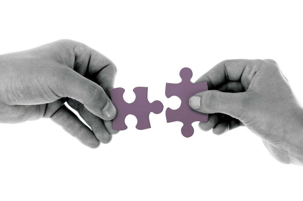 Hands putting together puzzle piece